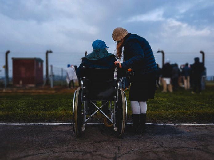 woman pushing another older woman in wheelchair